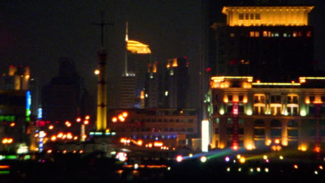 wide shot pan lit up buildings on waterfront with neon lights + spotlights / the bund, shanghai, china - スポットライト点の映像素材/bロール