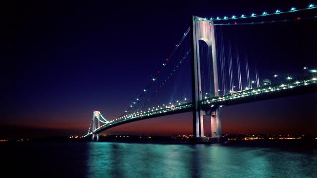 wide shot lit verrazano bridge over new york harbor / time lapse dusk to night / new york city - dusk to night stock videos & royalty-free footage