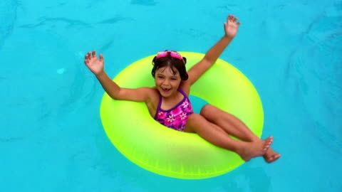 wide shot little girl floating in yellow inner tube in swimming pool - floating on water stock videos & royalty-free footage