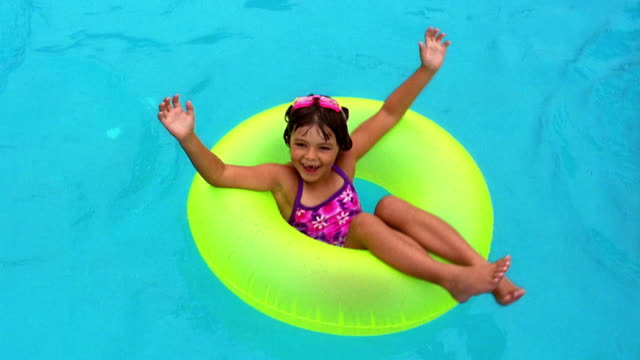 wide shot little girl floating in yellow inner tube in swimming pool - rubber ring stock videos & royalty-free footage