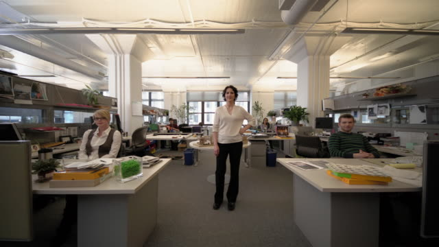 vídeos y material grabado en eventos de stock de wide shot lock down businesswoman standing in the middle of office, employees sitting at desks - toma ancha