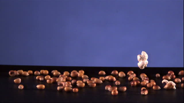 Wide Shot, Locked Down - A popcorn kernel pops in extreme slow motion / USA