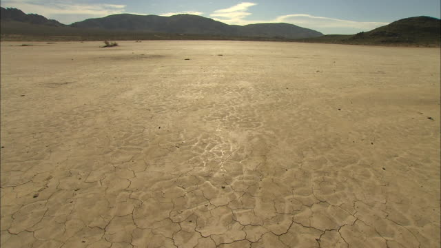 wide shot locked down -  flat, dry lakebed with hills in the background, cloud of dust blows by / california usa - horizont über land stock-videos und b-roll-filmmaterial
