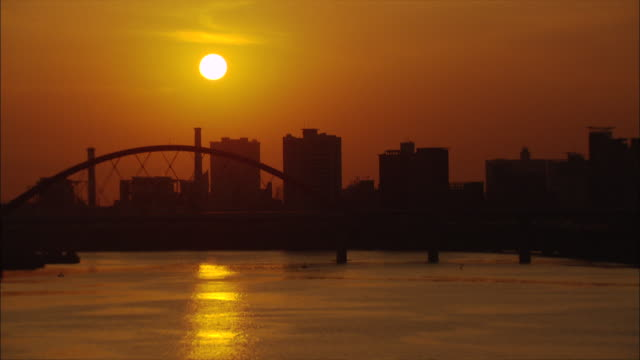 wide shot locked down - golden shimmering waters of the harbor with a bridge and apartment buildings in silhouette, setting sun / seoul south korea - establishing shot点の映像素材/bロール