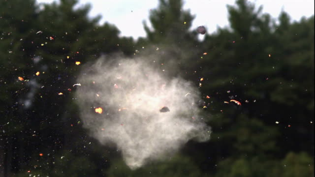 wide shot, locked down - pieces fly from a clay pigeon as it's hit by a shotgun shell / usa - tiro al piattello video stock e b–roll