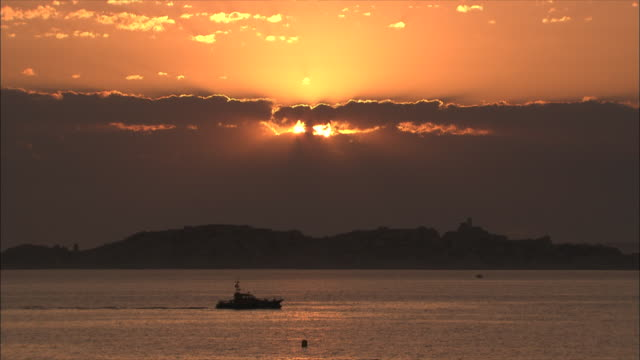 vidéos et rushes de wide shot locked down - setting sun bursts through clouds with golden light over small boat passing off the coast / marseille france - chalutier
