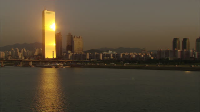 Wide Shot Locked Down - Shimmering waters of the harbor to a modern office building - the 63 Building - reflecting the setting sun like a bar of gold / Seoul South Korea