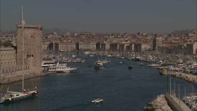 vidéos et rushes de wide shot locked down -  the old port of marseille, busy with boat traffic with marinas full of pleasure-boats and old city in background / marseille france - marseille