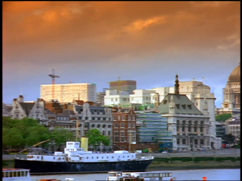 wide shot pan london skyline with st paul's cathedral / thames river + barge in foreground / orange filter - river thames stock videos & royalty-free footage
