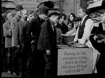 vidéos et rushes de 1909 b/w wide shot long of depressed customers having standoff with baker over increased price of bread  - 1900 1909