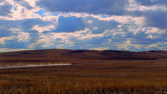 wide shot long shot car driving on desert road + leaving trail of dust behind / sand hills, nebraska - nebraska stock videos & royalty-free footage