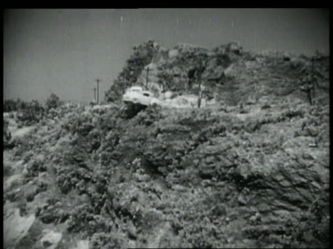 vidéos et rushes de b/w 1952 wide shot long shot car + truck collide on mountain road + fall off - accident de voiture