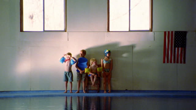 wide shot long shot four children in swimsuits with swimming gear on side of indoor pool / American flag on wall
