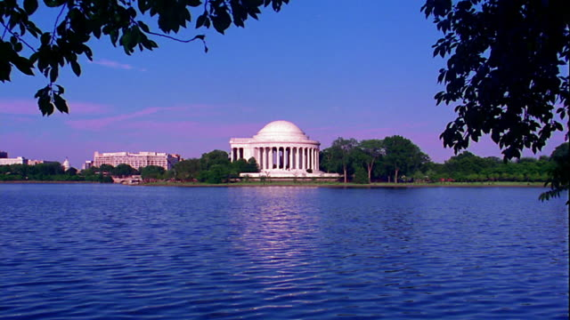 wide shot long shot jefferson memorial with trees + potomac river in foreground / washington, d.c. - jefferson memorial stock videos and b-roll footage
