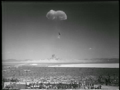 wide shot long shot mushroom cloud from h-bomb explosion over desert / yucca flats, nevada / newsreel - fallout nucleare video stock e b–roll