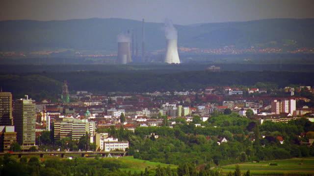 wide shot long shot nuclear power plant with low buildings in foreground / frankfurt, germany - kraftwerk stock-videos und b-roll-filmmaterial