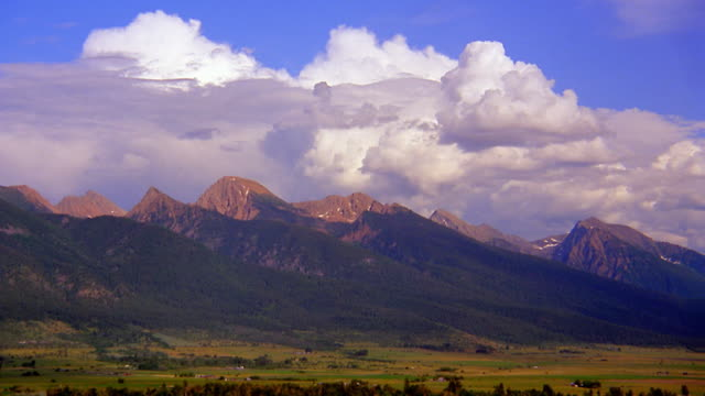 vidéos et rushes de wide shot long shot time lapse clouds forming over mountain range with grassy plain in foreground / montana - grandes plaines américaines