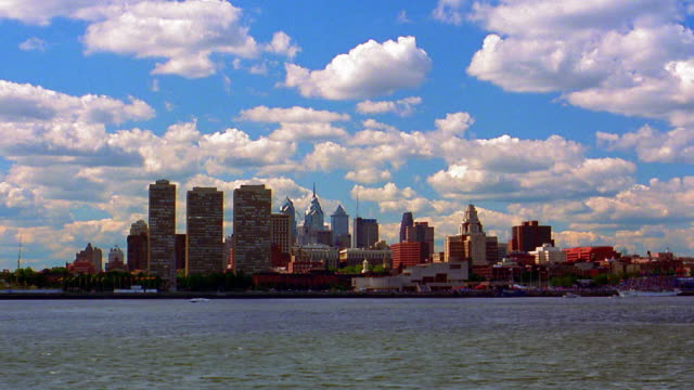 wide shot long shot time lapse clouds in blue sky over philadelphia skyline with delaware river in foreground / pennsylvania - 1993 stock-videos und b-roll-filmmaterial