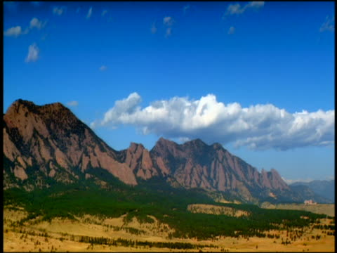 wide shot long shot time lapse clouds in blue sky over rocky mountains with trees at base / boulder, colorado - 巨礫点の映像素材/bロール