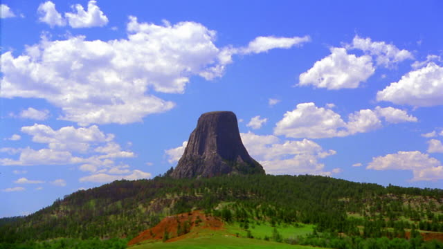 wide shot long shot time lapse clouds moving in sky behind devil's tower national monument / wyoming - wide stock videos and b-roll footage