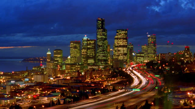 wide shot long shot time lapse clouds over silhouetted seattle skyline with traffic on highway in foreground / dusk to night / washington - seattle stock videos & royalty-free footage