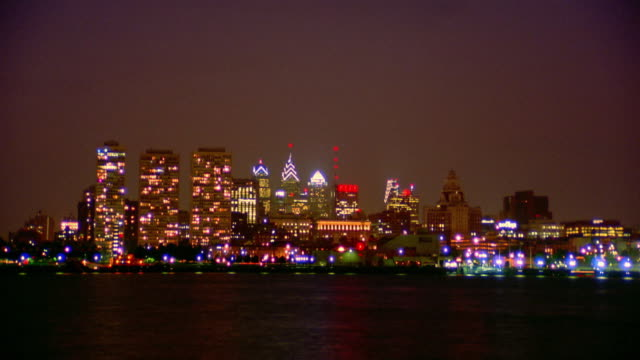 wide shot long shot time lapse philadelphia skyline at night with delaware river in foreground / pennsylvania - 離れた点の映像素材/bロール