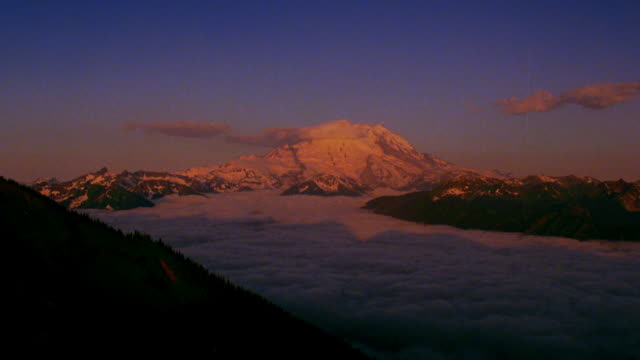 wide shot long shot time lapse sea of clouds over mountains with mt. rainier in background / sunlight gets brighter from sunrise - mt rainier stock videos & royalty-free footage
