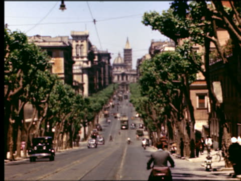 1949 wide shot long shot traffic on street leading to Santa Maria Maggiore (church) in background / Rome, Italy