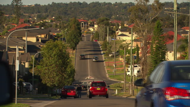 wide shot looking down suburban beaumont hills road and traffic including tradie utes passing / focus pull on suburban house rooftops high wide shot... - 引く点の映像素材/bロール