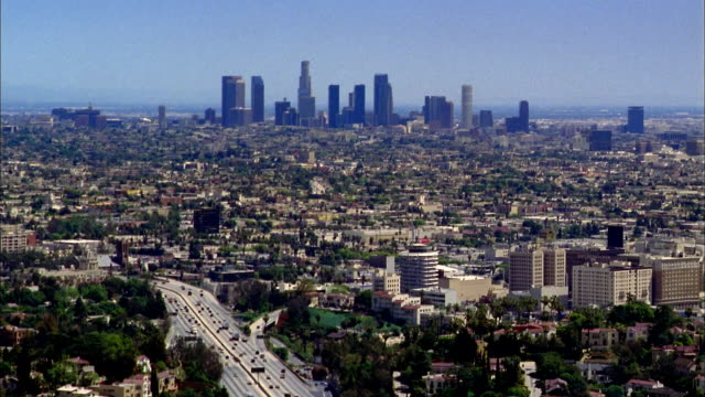 Wide shot Los Angeles city skyline and surrounding city w/freeway in foreground