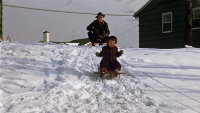 1954 wide shot low angle man pushing young girl on sled / girl sledding down slope past cam - single father stock videos & royalty-free footage