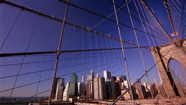 Wide shot low angle pan Brooklyn Bridge and suspension cables with skyline in background / NYC