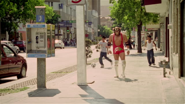 "wide shot luchador ""black tiger"" walking down street as two boys run by kicking soccer ball/ monterrey, mexico - verkleidung kleidung stock-videos und b-roll-filmmaterial"