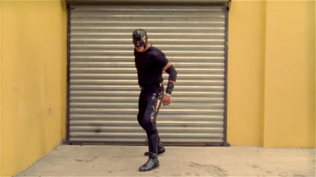 "wide shot luchador ""shadow"" facing garage door/ turning/ zoom in on mask/ monterrey, mexico - elbow pad stock videos & royalty-free footage"