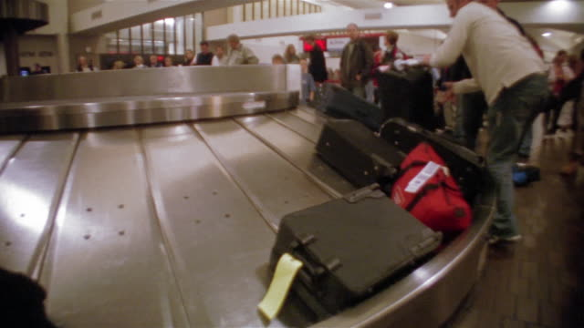 wide shot luggage passing by on carousel with people waiting / hartsfield airport, atlanta - reisegepäck stock-videos und b-roll-filmmaterial