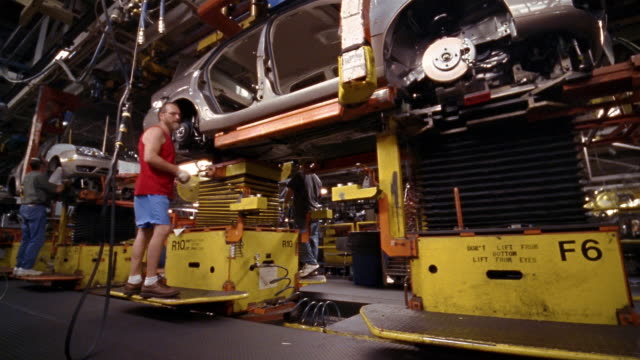 wide shot male factory workers assembling car on assembly line in car factory - car plant stock videos & royalty-free footage