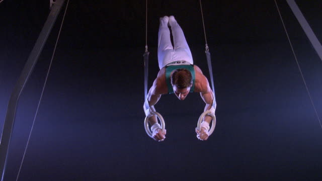 wide shot male gymnast performing on gymnastic rings - männliche person stock-videos und b-roll-filmmaterial