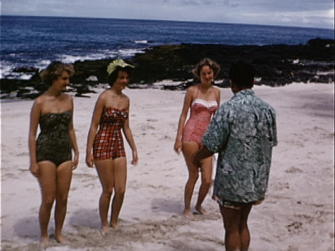 1953 Wide shot Male instructor teaching hula dancing to teenage girls and young woman on beach near ocean / Honolulu, Hawaii, USA