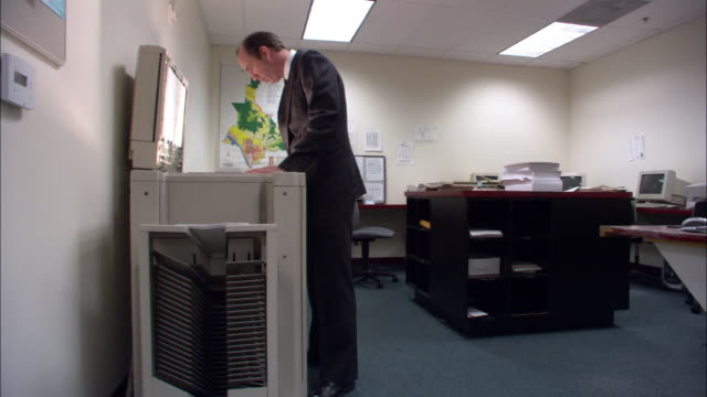 wide shot male office worker being mesmerized by flashing of photocopier / los angeles - photocopier stock videos and b-roll footage