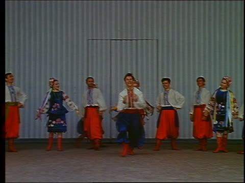 1967 wide shot male russian folk dancer jumping and doing splits with rest of troupe in background / russia - folk music stock videos and b-roll footage