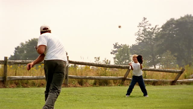 wide shot man and boy playing catch - throwing stock videos & royalty-free footage