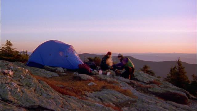 vídeos y material grabado en eventos de stock de wide shot man and woman camping on mountain / pan to mountains + valley with sun in background - tienda de campaña
