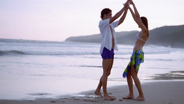 Wide shot man and woman dancing on beach