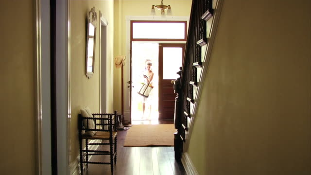 Wide shot man and woman entering door into hallway/ Roxbury, New York