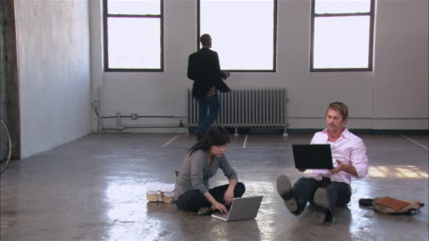 vidéos et rushes de wide shot man and woman having meeting with laptops on floor of empty loft space as other man dances in front of windows/ dancing man walking off/ brooklyn, new york - collègue