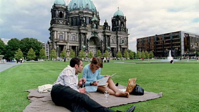 vidéos et rushes de wide shot man and woman having picnic on grass in front of the berlin cathedral / woman reading map - pelouse