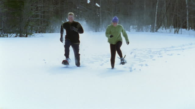 wide shot man and woman snowshoeing / running + kicking up snow behind them - winter sport stock videos & royalty-free footage