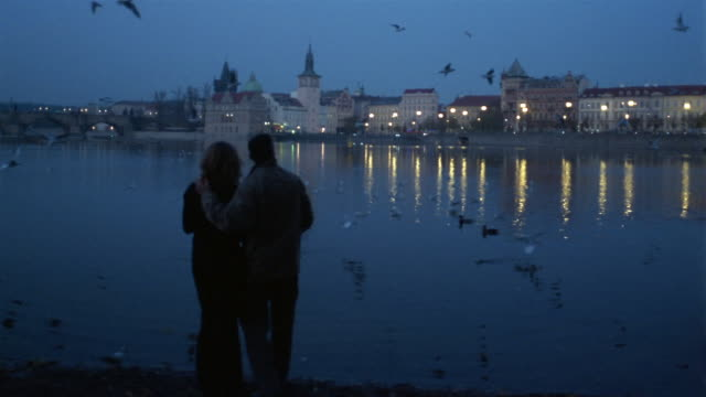 wide shot man and woman standing on bank of charles river / throwing bread at swans + ducks / prague - date night romance stock videos and b-roll footage