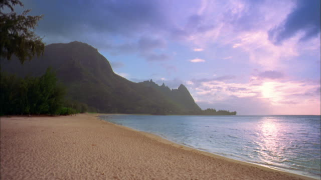 wide shot man and woman walking on beach w/calm surf + mountains in background - isola di kauai video stock e b–roll