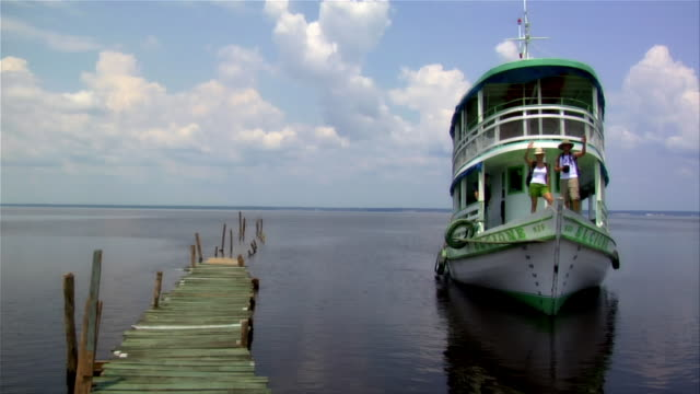 stockvideo's en b-roll-footage met wide shot man and woman waving from ferry boat as it approches pier / rio negro, brazil - color negro